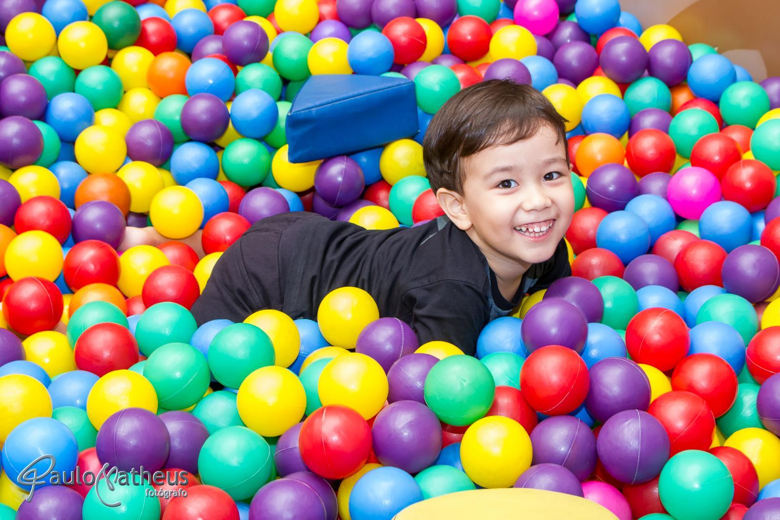 criança brincando na piscina de bolina por fotógrafo profissional