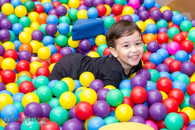 fotografia infantil de criança na piscina de bolinhas coloridas