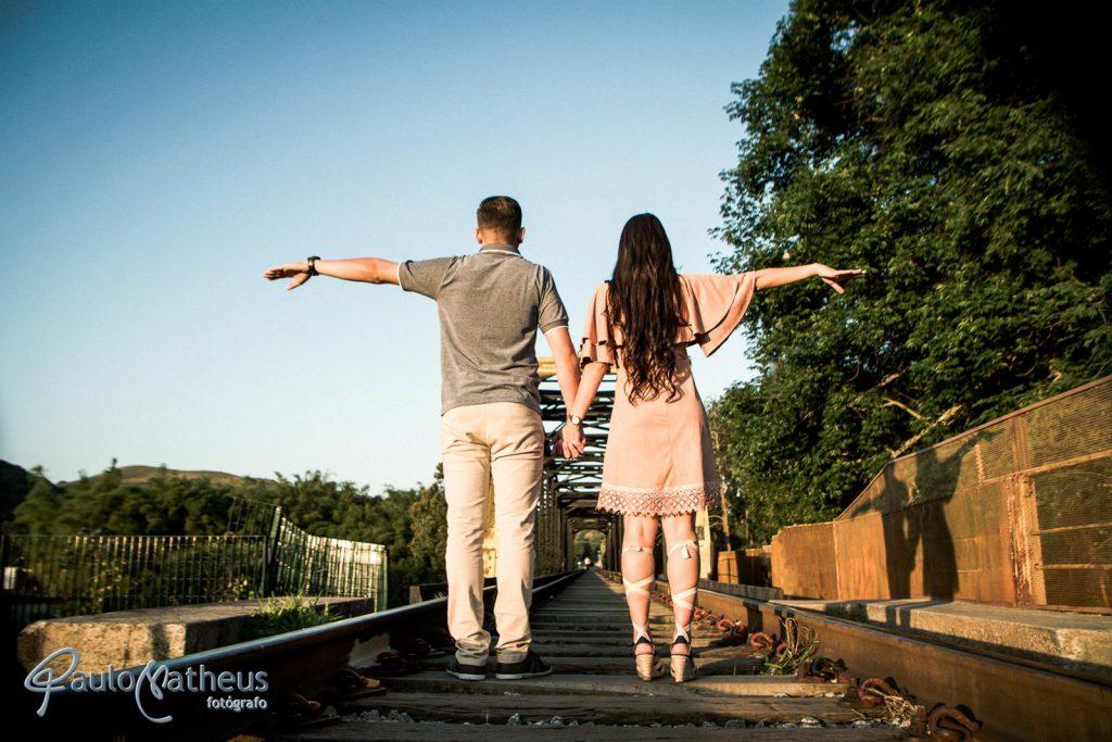 Fotografia na linha do trem em ensaio fotográfico para casal