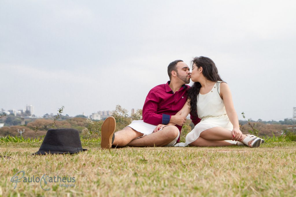 Casal sentado na grama em ensaio de casal no parque Villa Lobos